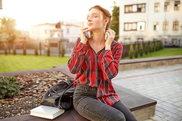 Junger schöner student, der kopfhörer eines karierten hemdes und einen rucksack stillstehen auf der straße trägt