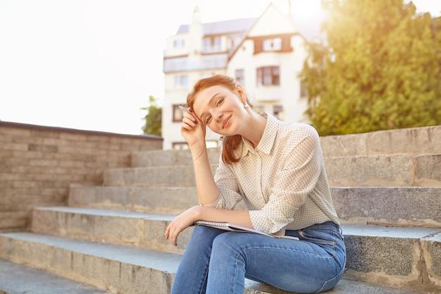 Junger schöner student schreibt einen aufsatz in ihr notizbuch, das auf der schritttreppe im freien sitzt