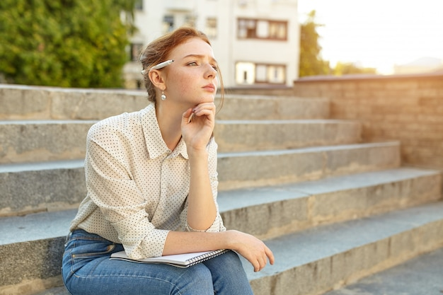 Junger schöner student schreibt einen aufsatz in ihr notizbuch