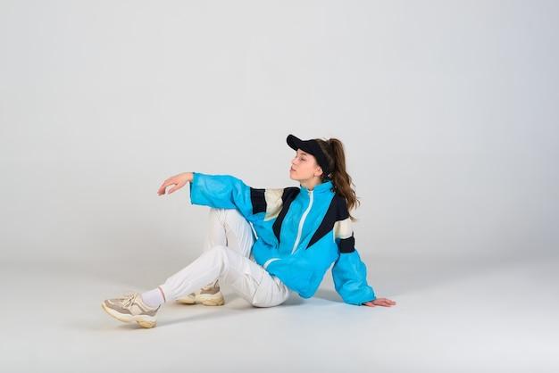 Junger schöner tänzer, der auf einem studiohintergrund aufwirft