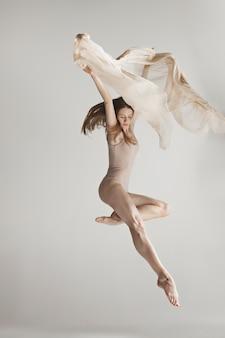 Junger schöner tänzer im beige badeanzug, der auf grau tanzt