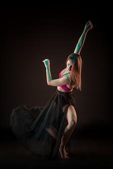 Junger schöner tänzer im beige kleid, das auf schwarz tanzt