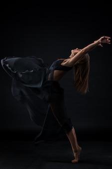 Junger schöner tänzer im beige kleid, das auf schwarzem hintergrund tanzt