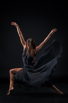 Junger schöner tänzer im beige kleid, das auf schwarzer wand tanzt
