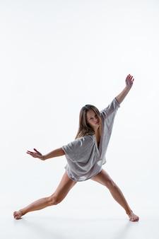 Junger schöner tänzer im beige kleid, das auf weiß tanzt