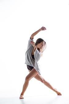 Junger schöner tänzer im beige kleid, das auf weißem hintergrund tanzt