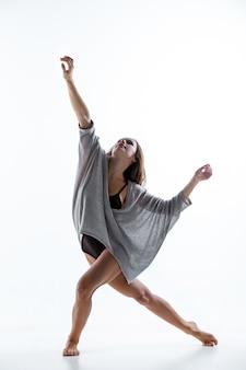 Junger schöner tänzer im beige kleidertanzen auf weißer wand