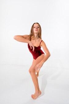 Junger schöner tänzer im roten badeanzug, der auf weißer wand tanzt