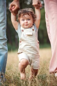 Junger schöner vater, mutter und kleiner kleinkindsohn gegen grüne bäume
