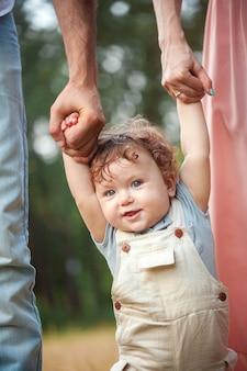Junger schöner vater, mutter und kleiner kleinkindsohn im freien