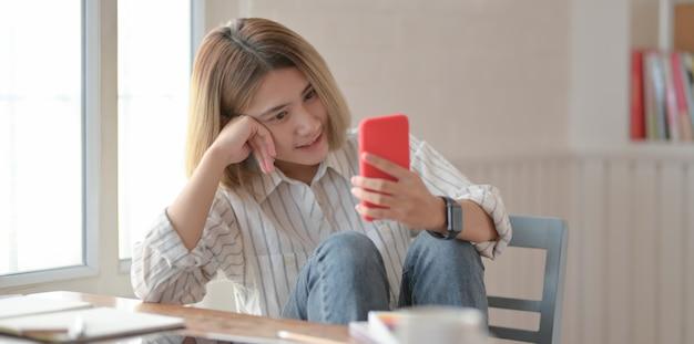 Junger schöner weiblicher designer, der smartphone betrachtet und auf dem stuhl sitzt