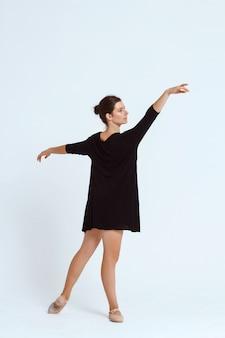 Junger schöner zeitgenössischer tänzer, der über weißer wand aufwirft