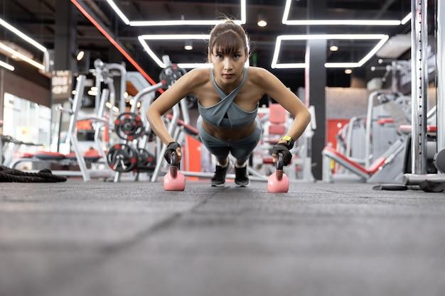 Junger schönheitsasiat, der übungen mit kettlebell tut. push-up auf gewichten im fitnessstudio.