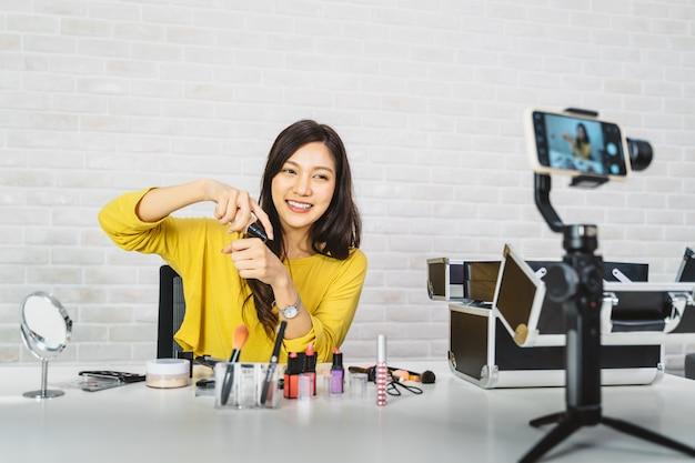 Junger schönheitsblogger, der make-uptutorial zeigt