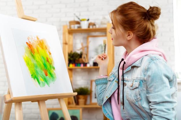 Junger schönheitskünstler, der abstrakte malerei auf einem gestell zeichnet