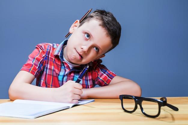 Junger schüler am schreibtisch, der hausaufgaben macht. kleines kind, das in notizbuch schreibt