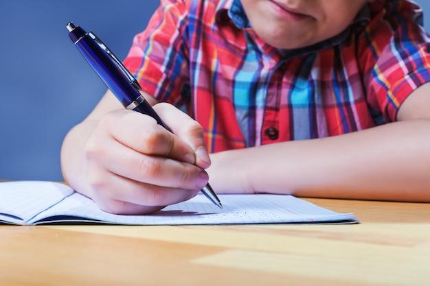 Junger schüler am schreibtisch, der in notizbuch-nahaufnahmeansicht schreibt. studieren im schulkonzept