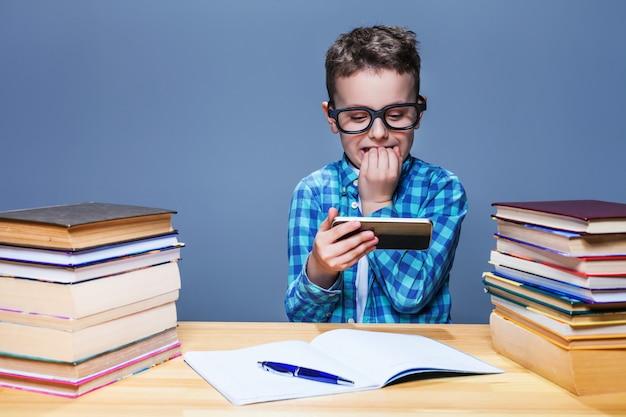 Junger schüler, der auf seinem telefon im klassenzimmer spielt
