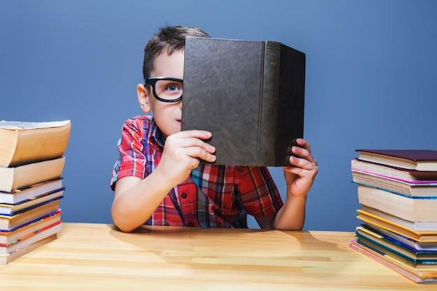 Junger schüler in gläsern, der wissen aus einem lehrbuch erhält. bildungskonzept