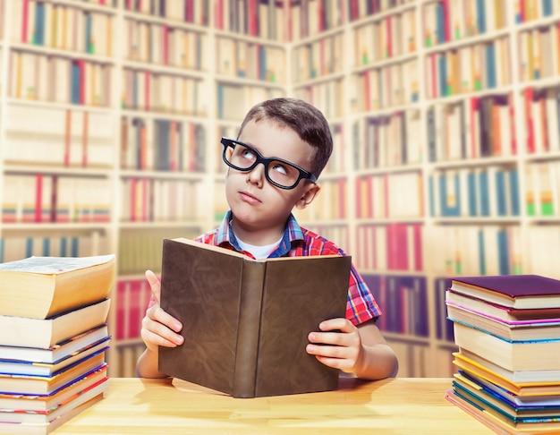 Junger schüler in gläsern, die ein buch in der schulbibliothek lesen. bildungskonzept. wissen aus einem lehrbuch holen