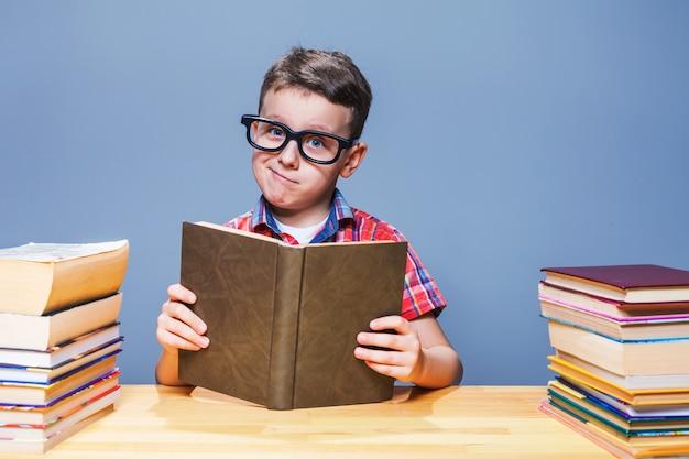 Junger schüler in gläsern, die ein buch in der schulbibliothek lesen. bildungskonzept