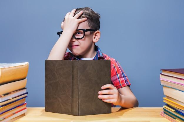 Junger schüler in gläsern mit buch, das an der schulbank sitzt. wissen aus einem lehrbuch holen
