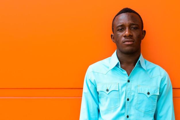 Junger schwarzafrikaner, der gegen orange gemalte wand lehnt