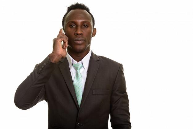 Junger schwarzafrikanischer geschäftsmann, der auf handy spricht