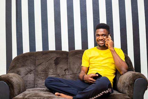 Junger schwarzafrikanischer mann, der mit dem handy telefoniert, mit freunden, die in seinem wohnzimmer sitzen