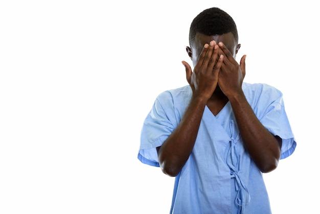 Junger schwarzafrikanischer mannpatient, der gesicht bedeckt