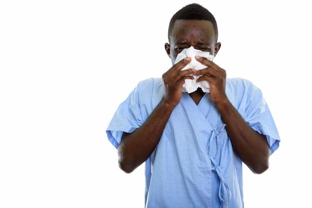 Junger schwarzafrikanischer mannpatient, der seine nase putzt