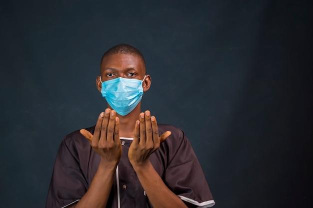 Junger schwarzafrikanischer muslimischer mann, der zu hause betet und die ausbreitung von covid 19 verhindert