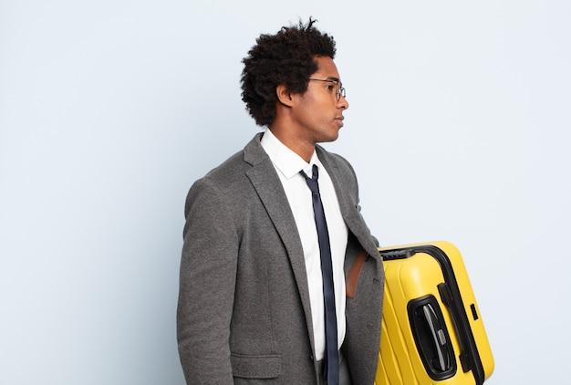 Junger schwarzer afro-mann auf profilansicht, der raum voraus kopiert, denkt, sich vorstellt oder träumt