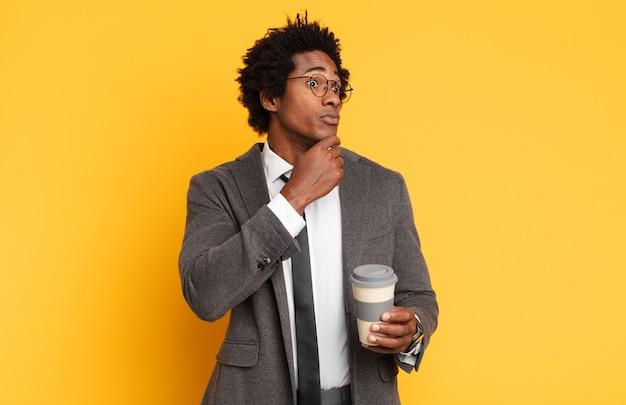 Junger schwarzer afro-mann denkt, fühlt sich zweifelhaft und verwirrt, hat verschiedene möglichkeiten und fragt sich, welche entscheidung er treffen soll