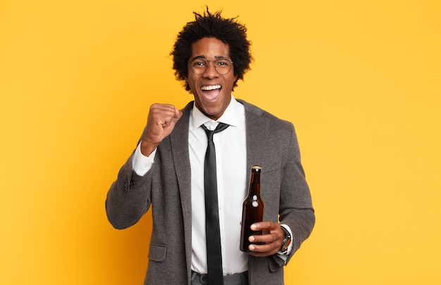 Junger schwarzer afro-mann, der aggressiv mit einem wütenden ausdruck oder mit geballten fäusten schreit, um erfolg zu feiern