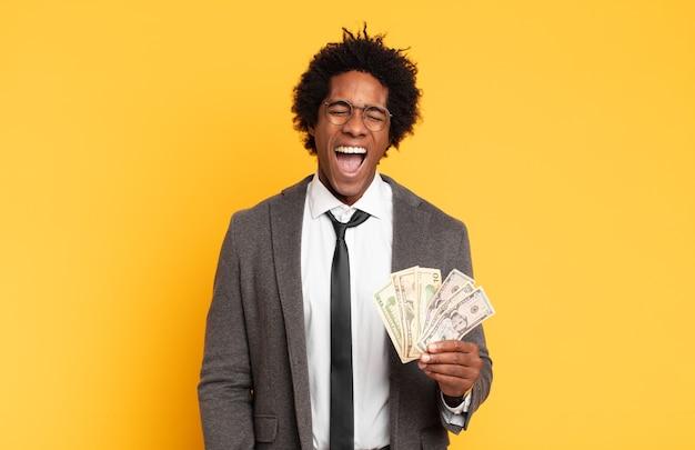 Junger schwarzer afro-mann, der aggressiv schreit, sehr wütend, frustriert, empört oder genervt aussieht und nein schreit
