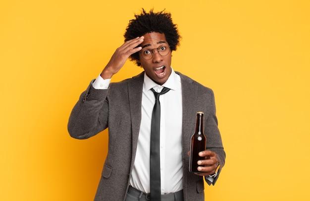 Junger schwarzer afro-mann, der glücklich, erstaunt und überrascht aussieht, lächelt und erstaunliche und unglaubliche gute nachrichten realisiert