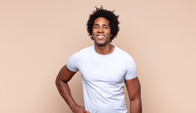 Junger schwarzer afro-mann, der glücklich mit einer hand auf hüfte und selbstbewusster, positiver, stolzer und freundlicher haltung lächelt