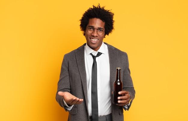 Junger schwarzer afro-mann, der glücklich mit freundlichem, selbstbewusstem, positivem blick lächelt und ein objekt oder konzept anbietet und zeigt
