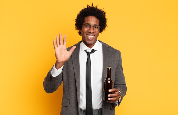 Junger schwarzer afro-mann, der glücklich und fröhlich lächelt, hand winkt, sie begrüßt und begrüßt oder sich verabschiedet
