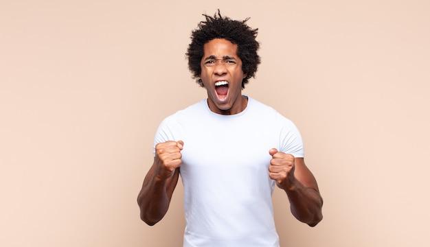 Junger schwarzer afro-mann, der konzentriert und meditierend aussieht, sich zufrieden und entspannt fühlt, denkt oder eine wahl trifft