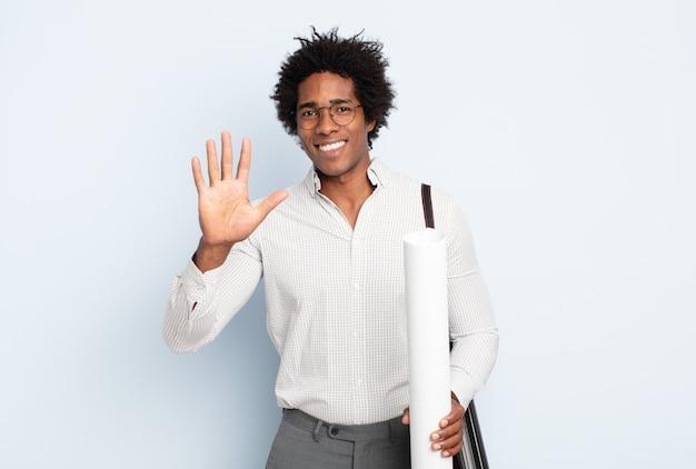 Junger schwarzer afro-mann, der lächelt und freundlich aussieht, die nummer fünf oder fünf mit der hand nach vorne zeigt und herunterzählt