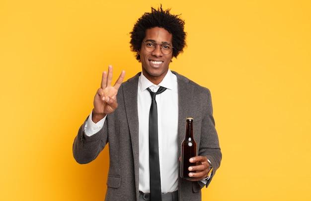 Junger schwarzer afro-mann, der lächelt und freundlich aussieht, nummer drei oder dritte mit der hand nach vorne zeigt, herunterzählt