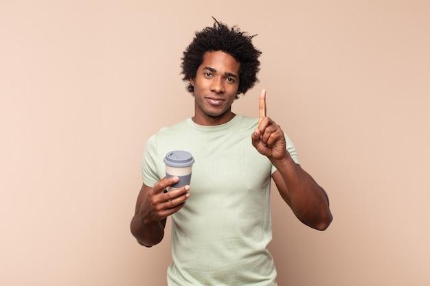 Junger schwarzer afro-mann, der lächelt und freundlich aussieht, nummer eins oder zuerst mit der hand nach vorne zeigt, herunterzählt