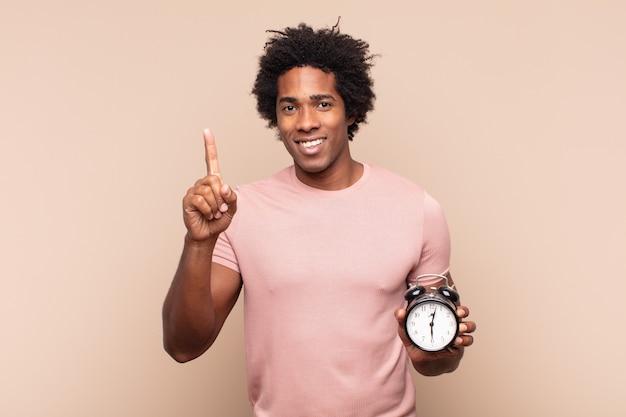 Junger schwarzer afro-mann, der lächelt und freundlich aussieht, nummer eins oder zuerst mit der hand vorwärts zeigend, herunterzählend