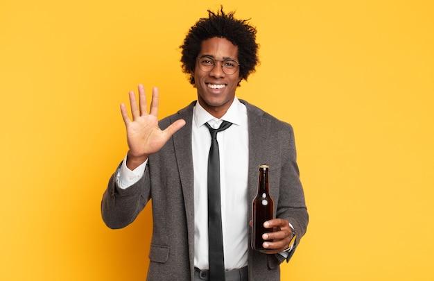 Junger schwarzer afro-mann, der lächelt und freundlich aussieht, nummer fünf oder fünften mit der hand vorwärts zeigend, herunterzählend