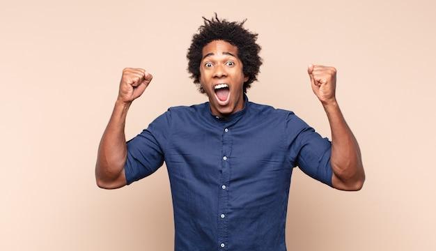 Junger schwarzer afro-mann, der lächelt und sich entspannt, zufrieden und sorglos fühlt, positiv lacht und kühlt