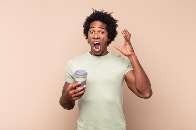 Junger schwarzer afro-mann, der mit den händen in der luft schreit und sich wütend, frustriert, gestresst und verärgert fühlt