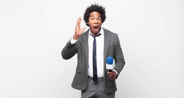 Junger schwarzer afro-mann, der mit den händen in die luft schreit und sich wütend, frustriert, gestresst und verärgert fühlt