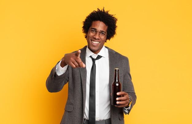 Junger schwarzer afro-mann, der mit einem zufriedenen, selbstbewussten, freundlichen lächeln auf kamera zeigt und sie wählt
